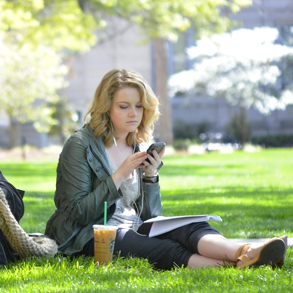 A female student checks her phone on the Mizzou campus.