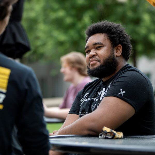 Student is photographed sitting at an outdoor table