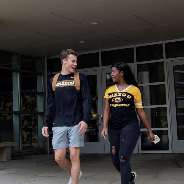 Two students are photographed talking to each other as they exit the MU Student Center