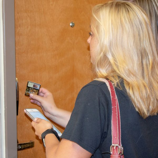 A student uses a student ID card to enter a room