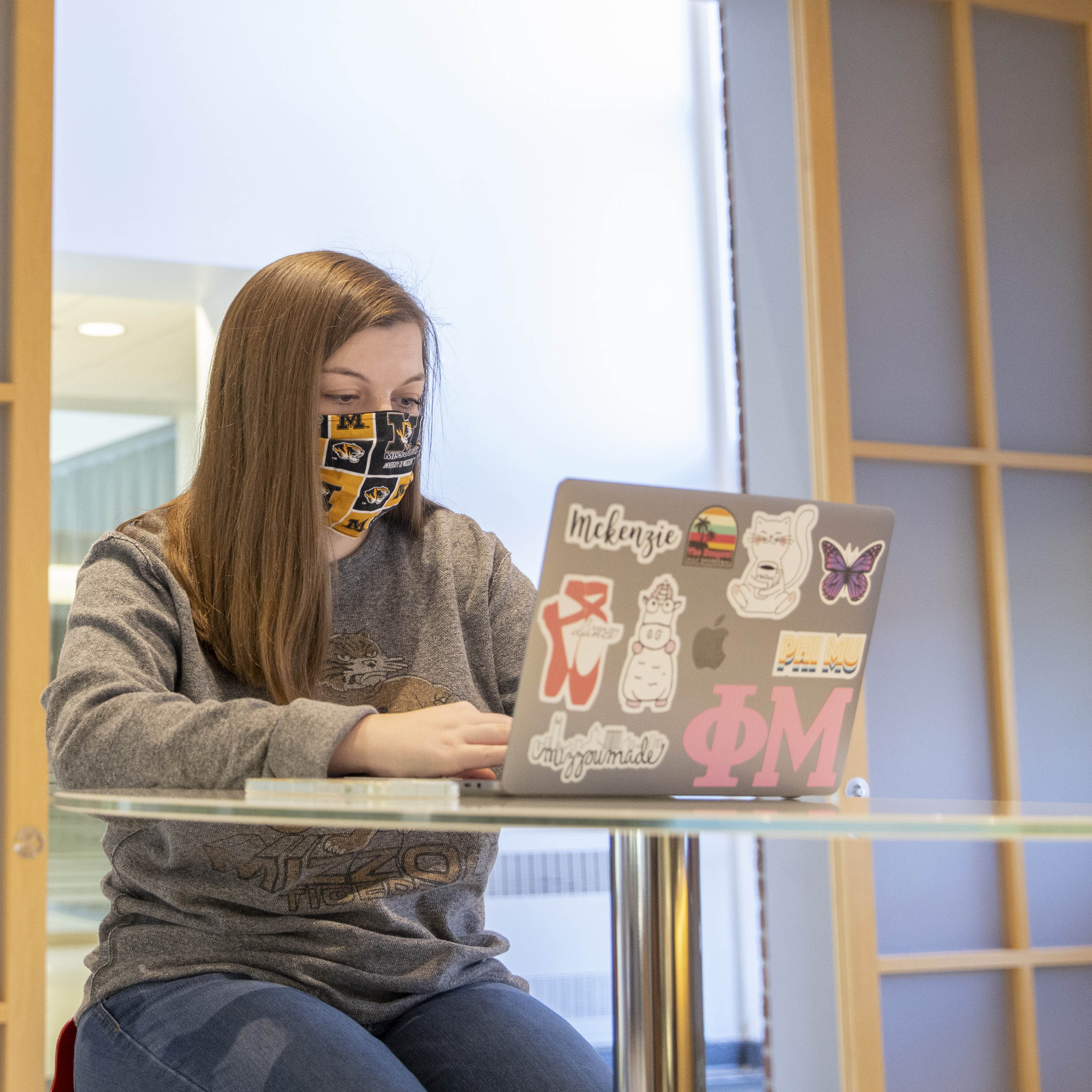 Student wearing face mask studying indoors
