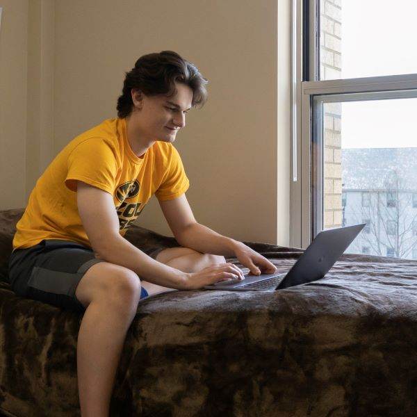 a student sits on a bed in a residence hall room while using a laptop computer